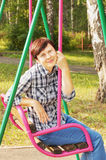 Woman sits on a swing Stock Photo