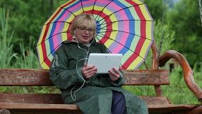 Woman sits on swing bench with multicolor umbrella in green raincoat stock video