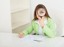 Woman sits at table with big magnifier in hands Royalty Free Stock Photos