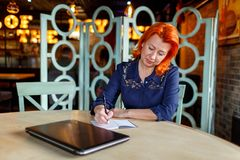 A woman sits at a table in a cafe and makes notes in a notebook bending the globe. A woman, aged, red-haired, in a blue dress sits at a table in a cafe and makes Royalty Free Stock Image