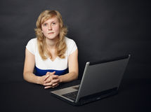 Woman sits at table with computer Stock Image