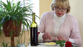 Woman sits at a table drinking red wine and eating cheese stock video footage