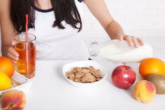 Woman sits at a table and eat breakfast. Women eating healthy food for breakfast. Fruit, cereal and milk, close up selective focus Stock Photos