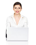 Woman sits from the  table with laptop in white shirt Stock Photo