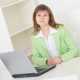Woman sits at table at light office with lap Stock Image