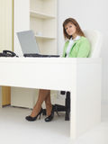 Woman sits at table at light office with laptop Stock Photography