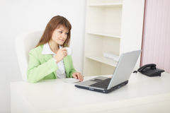 Woman sits at table at light office with laptop Royalty Free Stock Photos