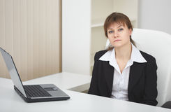 Woman sits at table at light office with laptop. The serious woman sits at a table at light office with the laptop stock images
