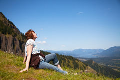 Woman sits at the top of a cliff Stock Photo