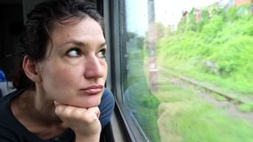 Woman sits in train near window during movement stock video footage