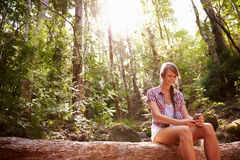 Woman Sits On Tree Trunk In Forest Using Mobile Phone Stock Photo