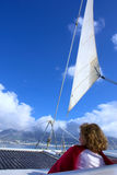 Woman sits under sail Stock Photography