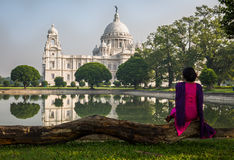 A woman sits at the Victoria Memorial architectural building garden beside the south lake Royalty Free Stock Image