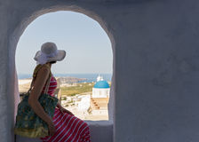 Woman sits on a wall, island Santorini Royalty Free Stock Photos
