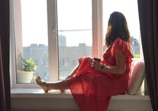 A woman sits on a window seat in the summer sun and looks out at the street