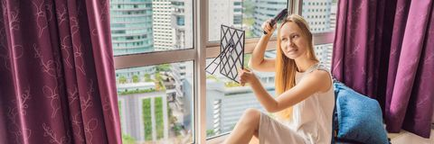 Woman sits by the window and uses an electronic hairbrush BANNER, LONG FORMAT. Woman sits by the window and uses an electronic hairbrush. BANNER, LONG FORMAT stock photos