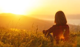 Free Woman Sits With Her Back In The Field And Look Sunset In The Mou Royalty Free Stock Images - 110244389