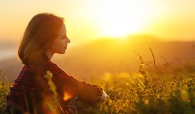 Free Woman Sits With Her Back In The Field And Look Sunset In The Mou Royalty Free Stock Photo - 110764735