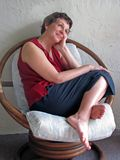 Woman sitting. On porch in wicker chair Royalty Free Stock Images