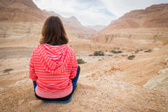 Woman sitting above desert valley. Royalty Free Stock Photos