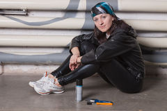 Woman sitting against a brick wall with graffiti Royalty Free Stock Images