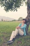 Woman sitting against tree Stock Photos