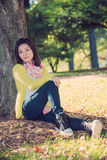 Woman sitting against a tree. Portrait of happy looking woman sitting against a tree Stock Images