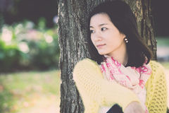 Woman sitting against a tree Royalty Free Stock Photo