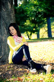 Woman sitting against a tree Stock Image