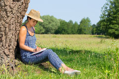 Woman sitting against tree writing in nature Stock Images