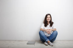 Woman sitting against the wall on the floor is notebook. Smiling beautiful woman finished work contentedly sitting against the wall on the floor is closed Royalty Free Stock Image