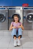 Woman Sitting Against Washing Machines At Laundry Stock Image