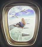 Woman sitting on airliner wing and looks at dolphins Royalty Free Stock Image