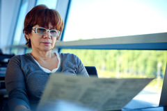 Woman sitting in the airport cafe and waiting for departure. Royalty Free Stock Photo