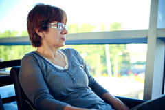 Woman sitting in the airport cafe and waiting for departure. Royalty Free Stock Photos