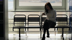 The woman is sitting in airport waiting hall waiting for someone. The woman is sitting in airport waiting hall on black trellis seat waiting for someone looking stock video