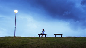 Woman sitting alone in a bench Stock Image