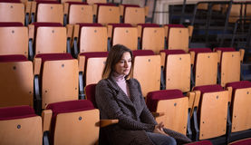 Woman sitting alone in empty cinema house Stock Photos