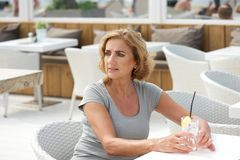 Woman sitting alone with a glass of water at restaurant Stock Images