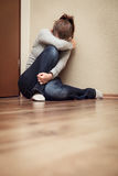 Woman sitting alone at the ground, domestic violence at home Stock Photography