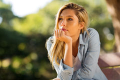 Woman sitting alone outdoors Royalty Free Stock Image