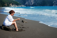 Woman sitting  alone on the rock at the beach Stock Photography