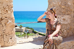 Woman sitting on ancient wall Royalty Free Stock Image