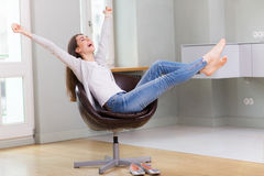Woman sitting in armchair, arms outstretched Stock Photography
