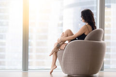 Woman sitting in the armchair royalty free stock images