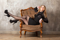 Woman sitting in armchair Stock Image