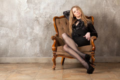 Woman sitting in armchair Stock Photo