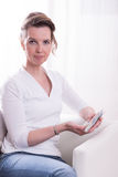 Woman sitting in armchair and counting money Royalty Free Stock Photography