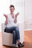 Woman sitting in armchair and counting money is happy Stock Image