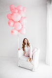 Woman sitting in an armchair and holding a bunch of pink balloons Royalty Free Stock Photography